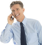 Happy Businessman Answering Smart Phone. Happy mature businessman looking away while answering smart phone against white background Royalty Free Stock Photos
