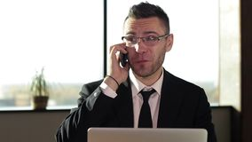 Happy businessman answering smart phone while using laptop stock video footage