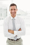 Happy businessman with arms crossed in office Royalty Free Stock Photography