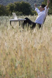 Happy businessman with arms raised looking at laptop on table in rural field Stock Photos