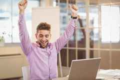 Happy businessman with arms raised. Sitting by laptop on table in office Stock Images
