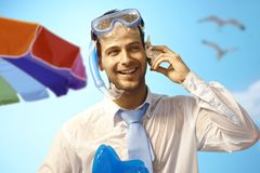 Happy businessman on the beach. Happy young businessman on summer holiday listening to murmur of sea in seashell Royalty Free Stock Images