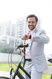Happy businessman with bicycle checking time outdoors Stock Photo