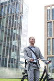 Happy businessman with bicycle standing outside office building Royalty Free Stock Photos