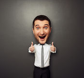 Happy businessman with big head laughing. Happy businessman with big head showing two thumbs up and laughing. funny picture over dark background Stock Photo