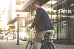 Happy businessman on a bike. Business man leaving his work. From royalty free stock photos