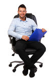 Happy businessman in a black leather chair Stock Image
