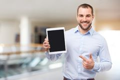 Man in blue shirt shows touch screen in a business center. Happy businessman in blue shirt shows touch screen in a business center royalty free stock photo