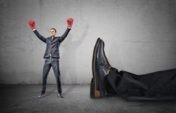 A happy businessman with boxing gloves on arms raised in victory stands near a giant male leg fallen down. Fight off competition. Unexpected winner. Chance of stock photo