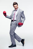 Happy businessman in boxing gloves. Full length portrait of a happy businessman in boxing gloves over gray background Royalty Free Stock Photo