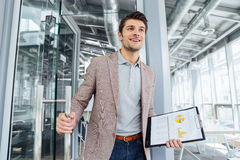 Happy businessman with business plan entering the door in office. Happy young businessman with business plan on clipboard entering the door in office Royalty Free Stock Photography