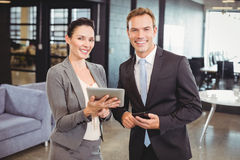 Happy businessman and businesswoman with digital tablet and mobile phone Stock Photo