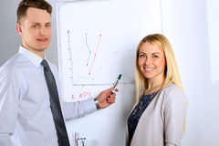Happy Businessman  with businesswoman giving a presentation on flipchart. Teamwork concept Royalty Free Stock Image