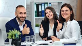 Happy businessman and businesswoman smiling showing cool thumb up enjoying corporate meeting