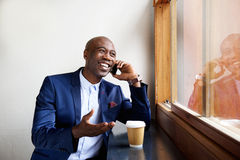 Happy businessman at a cafe talking on cell phone Stock Photography