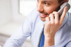 Happy businessman calling on phone at office Stock Image