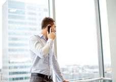 Happy businessman calling on smartphone in office Royalty Free Stock Photo