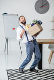 Businessman with cardboard box in hands quitting job. Happy businessman with cardboard box in hands quitting job Royalty Free Stock Image