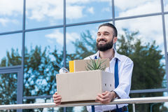Businessman with cardboard box with office supplies in hands standing outside office building, quitting job concept. Happy businessman with cardboard box with Royalty Free Stock Images