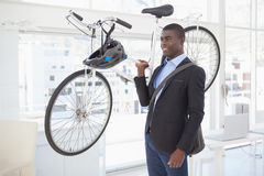 Happy businessman carrying his bicycle Stock Photography