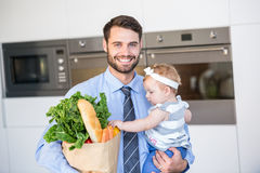 Happy businessman carrying vegetables and daughter Royalty Free Stock Image