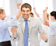 Happy businessman with cash money in office Stock Image