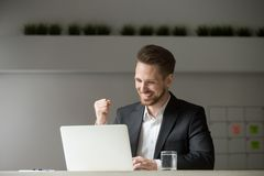 Happy businessman celebrating business success online win lookin. Happy young businessman in suit looking at laptop excited by good news online, lucky successful Stock Photo