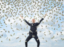Happy businessman in celebrating pose with loads of money in the air royalty free stock images