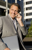 Happy businessman on cellphone. A handsome forties businessman is chatting on his cellphone while holding a laptop computer under his arm.His office building is Royalty Free Stock Photography