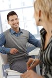 Happy businessman chatting. With female colleague at work, smiling stock images