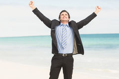 Happy businessman cheering at the beach Stock Images