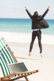 Happy businessman cheering at the beach Stock Image
