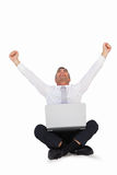Happy businessman cheering and sitting with his laptop Stock Images
