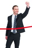 Happy businessman with clenching fist crossing the finish line Stock Photo