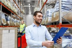 Happy businessman with clipboard at warehouse. Logistic business, shipment and people concept - happy businessman with clipboard and worker loading goods by Stock Images