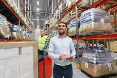 Happy businessman with clipboard at warehouse. Logistic business, shipment and people concept - happy businessman with clipboard and worker loading goods by Royalty Free Stock Photography