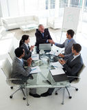 Happy businessman closing a deal. At the end on a meeting with their team Royalty Free Stock Photo