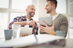 Happy businessman with colleague using digital tablet in office Royalty Free Stock Photo