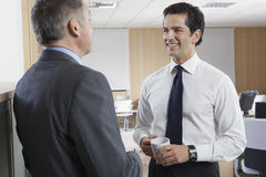 Happy Businessman Communicating With Colleague Stock Photo