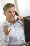 Happy Businessman Communicating On Telephone While Looking At Co. Happy mature businessman communicating on telephone while looking at computer monitor in office Royalty Free Stock Photo