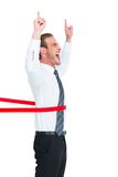 Happy businessman crossing the finish line and pointing up Royalty Free Stock Images