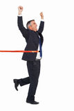 Happy businessman crossing finishing line Stock Photo