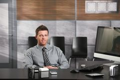 Happy businessman at desk. Portrait of happy businessman sitting at office desk, looking at camera, smiling Royalty Free Stock Photo