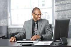 Happy businessman at desk. Portrait of happy smart black businessman sitting at desk in office, smiling Royalty Free Stock Images