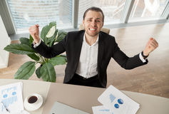 Happy businessman at desk celebrating achievements. Funny emotional businessman with clenched teeth raising hands in great joy because of unbelievable success Royalty Free Stock Image