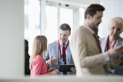 Happy businessman discussing with colleague in convention center.  stock image