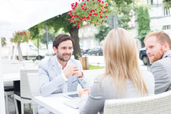 Happy businessman discussing with colleagues at sidewalk cafe Stock Photo