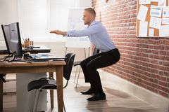 Businessman Doing Exercise In Office. Happy Businessman Doing Exercise In Front Of Computer At Office royalty free stock photography