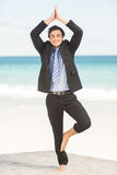 Happy businessman doing yoga Stock Images