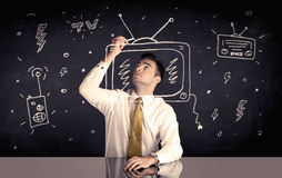 Happy businessman drawing tv and radio. An elegant happy businessman drawing a television around his face, dreaming about becoming a famous actor or a programme Stock Photography